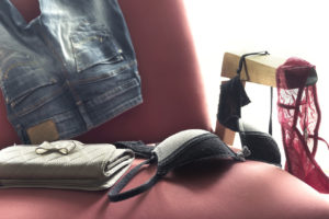 Female lingerie and clothes on armchair