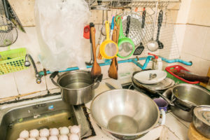 untidy Kitchenware ; Pile of dirty dishes in sink and counter in the kitchen