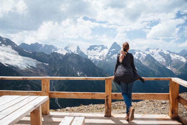 Woman relaxing on terrace on mountain, alpine view, snow on hills. Dombay, Karachay-Cherkessia, Caucasus, Russia.