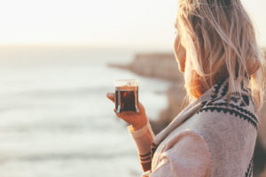 Woman wearing sweater drinking hot tea outdoors in autumn sunlight. Fall cozy concept, backlit.