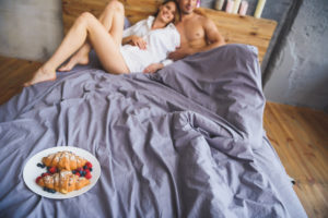 close up of breakfast on a couch while blurred couple in the background hugging
