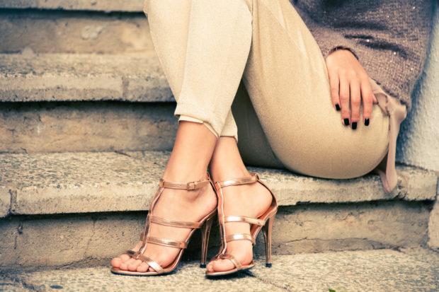 woman legs in high heel golden sandals sit on stairs, outdoor shot