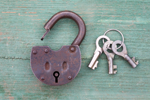 Old rusty padlock and key on wood background
