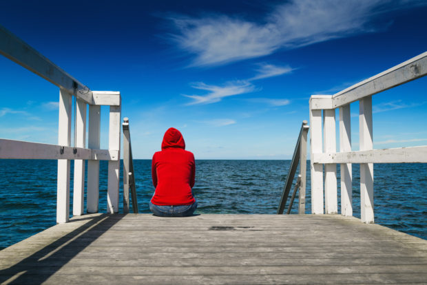 Alone Young Woman in Red Hooded Shirt Sitting at the Edge of Wooden Pier Looking at Water - Hopelessness, Solitude, Alienation Concept