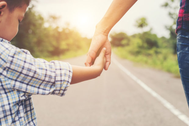 Mother holding hand of her son outdoors in summer walking on the roadside.