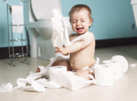 A Toddler ripping up with toilet paper in bathroom