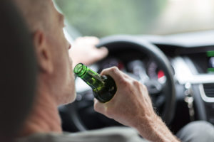 Man drinking a beer while driving