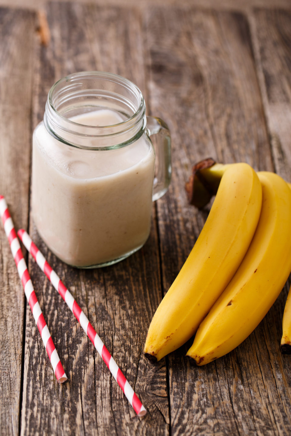 Delicious banana smoothie in glass jar with drinking straw and bananas on table.
