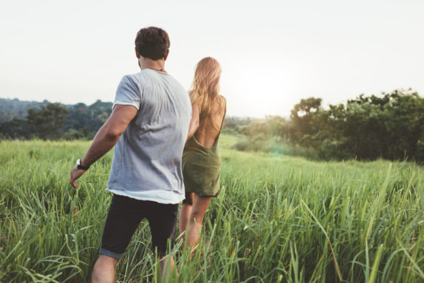 Rear view of a young couple strolling in a grass field. Young man and woman walking together in rural landscape.
