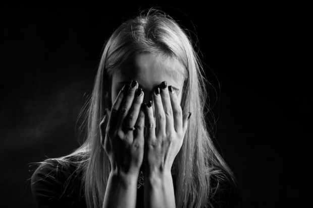 crying woman covering face with her hands, monochrome
