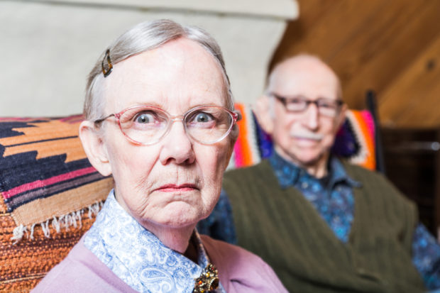 Old couple seating in livingroom woman scowling