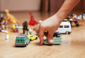 children playing toys on floor at home, little hand in mess