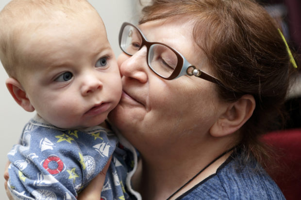 Smiling grandmother kissing her grandson at home