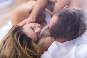 Young lovers during foreplay before morning sex