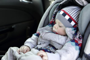 Toddler sleeping in baby car seat at day