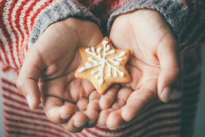 Decorated Christmas cookie in child hands
